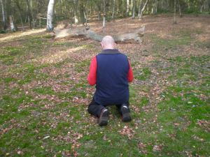 Midlife guy on his knees in the woods