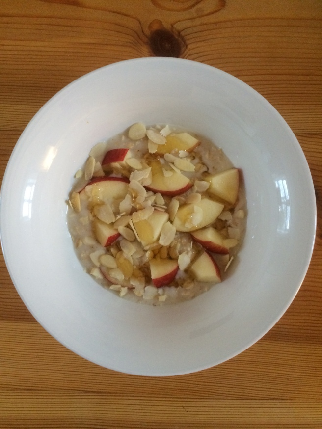 Whole oat porridge with apple, almonds, coconut milk and wildflower honey